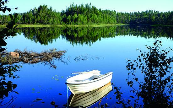 En båt ligger på en spegelblank sjö och runtomkring syns granar.