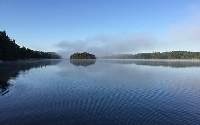 En sjö, borta i horisonten syns träd.